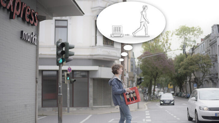 Woman at traffic light carries beverage crate and has thought bubble with robot in it